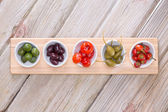 Assorted olives and peppers on taster plates — Stock Photo