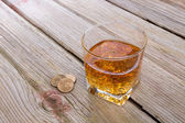 Tumbler of whiskey and tip on a bar counter — Stock Photo