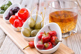 Savory peppers and olives served with whiskey — Stock Photo