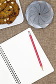 Open notebook with nut cookies and a gift — Stock Photo