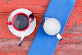 Cup of black coffee on a rustic red picnic table — Stock Photo