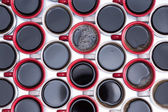 Pattern of black coffee in red and white mugs — Stock Photo