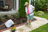 Older lady doing cleaning work in the yard — Stock Photo