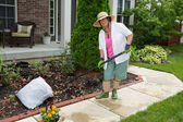 Old lady at work in the garden cleaning flowerbeds — Stock Photo