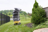 Mulch in bags piled high on a cart in the garden — Stock Photo