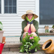 Elderly woman pausing while potting up plants — Stock Photo #48954047