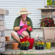 Senior lady potting up plants in flowerpots — Stock Photo #48956117