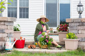 Grandmother potting up plants on her patio — Stock Photo