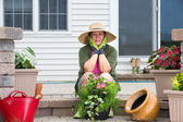 Elderly woman pausing while potting up plants — Stock Photo