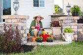 Happy elderly Grandma potting up plants — Stock Photo