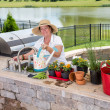 Retired senior woman gardening, in a brick patio — Stock Photo #49169783