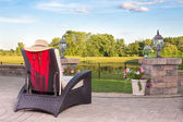 Vacant wicker armchair overlooking a tranquil pond — Stock Photo