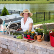 Attractive senior woman caring for her pot plants — Stock Photo #49220821