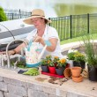 Lady filling a watering can on an outdoor patio — Stock Photo #49220993