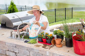 Lady filling a watering can on an outdoor patio — Stock Photo
