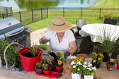 Lady gardener potting up new plants on a patio — Stock Photo
