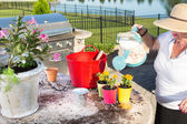 Senior lady watering newly potted plants — Stock Photo