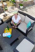 Stylish senior woman drinking on a patio — Stock Photo