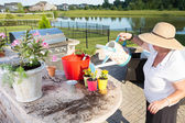 Senior lady watering her newly potted plants — Foto de Stock