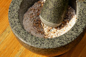 Corn being grinded with mortar and pestle — Stock Photo