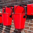 Three red fire buckets wall mounted — Stock Photo #27497099
