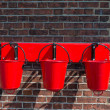 Three red fire buckets wall mounted — Stock Photo