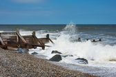 Waves breaking onto a shingle beach with groynes — Stock Photo