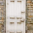 Stock Photo: Old external door in stone wall