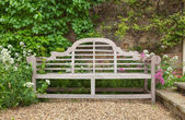 Weathered garden bench in landscaped setting — Stock Photo