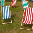 Canvas deckchairs on a grassy lawn in the summer. — Stok fotoğraf
