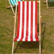 Canvas deckchairs on a grassy lawn in the summer. — Stock Photo