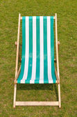 Canvas deckchair on a grassy lawn in the summer. — Stock Photo
