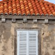 Building with orange roof tiles and wodden shuttered window — Стоковая фотография