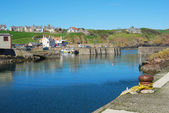 The harbour entrance, boats and village at St. Abbs, Berwickshir — Foto Stock