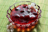 Cherry preserves with flowers — Stock Photo
