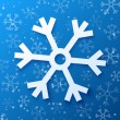Paper abstract snowflake on blue background — Stock Vector