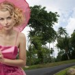 Beautiful blonde woman with sun umbrella in the thai park — Stock Photo