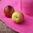 Pink hat and nectarines on the sand — Stock Photo