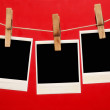 Blank instant photo hanging on the clothesline isolated on red background — Stock Photo