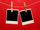 Old photos hanging on the clothesline isolated on red — Stock Photo