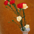 Yellow and red carnations in vase on a wooden background — Stock Photo