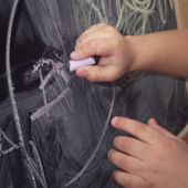Child draws with chalk on the blackboard — Stock Photo