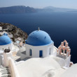 Blue domes and their bell tower in Oia. Santorini — Stock Photo