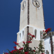 Clock tower and flowers on blue sky, Greece — Stock Photo