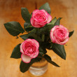 Pink roses in vase on a wooden table - Stock Photo