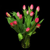 Bouquet of pink tulips in a vase on black — Stock Photo