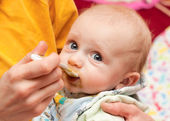 Baby eating from a spoon — Stock Photo