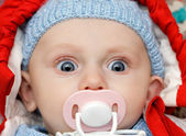 Baby with dummy, looks funny — Stock Photo