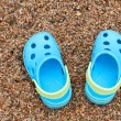 Blue sandals slippers on the sand — Stock Photo