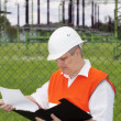 Stock Photo: Engineer with folder near electricity substation